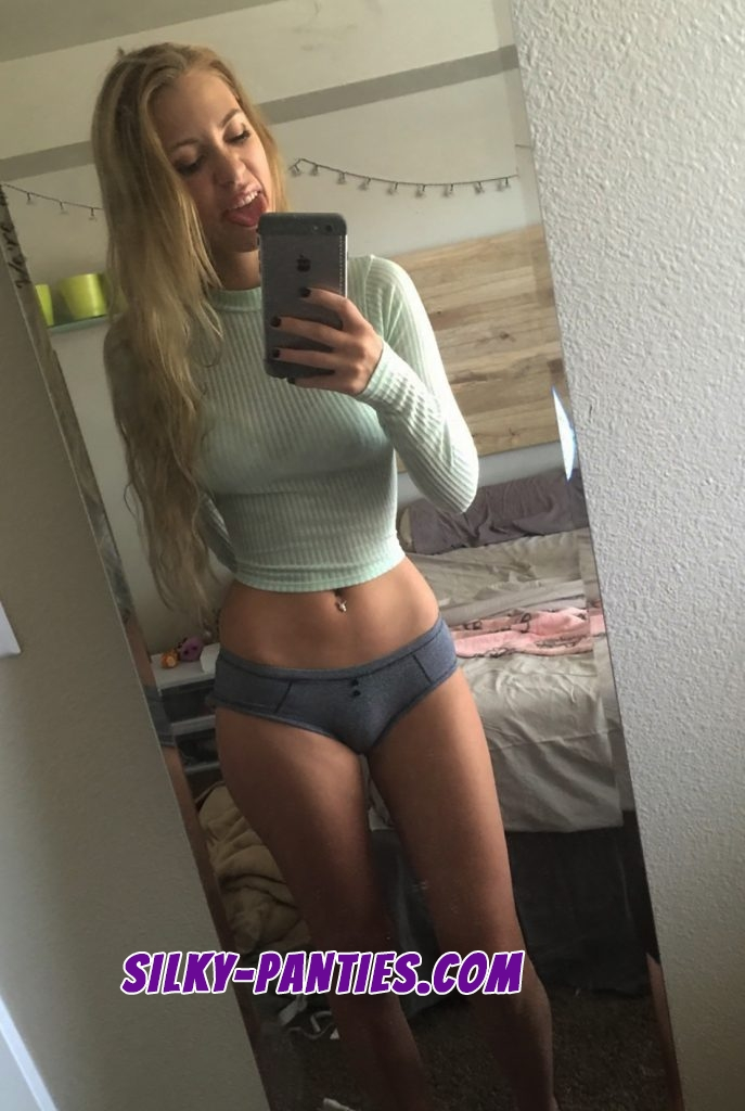 Gorgeous girl pops her tongue out while doing a selfie in mirror